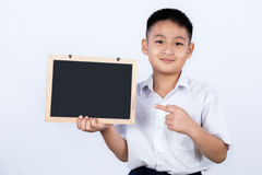 Estudante vestindo Uniform Pointing Chalkb de Little Boy do chinês asiático imagem de stock
