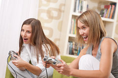 Estudantes - adolescente de duas fêmeas que joga o jogo da tevê Imagem de Stock