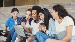 Estudantes adolescentes emocionais que olham excitados no port?til foto de stock royalty free