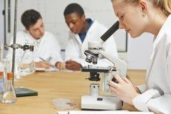 Estudantes adolescentes na classe da ciência que usa o microscópio imagens de stock