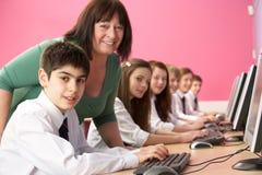 Estudantes adolescentes nELA classe que usa computadores fotografia de stock