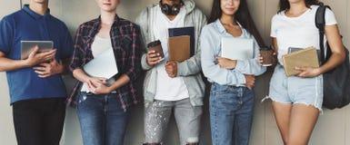 Estudantes adolescentes que guardam livros e dispositivos nas m?os foto de stock