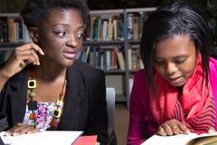 Estudantes afro-americanos em uma biblioteca de faculdade Imagem de Stock Royalty Free