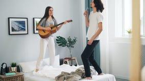 Estudantes alegres que cantam na dança de jogo de controle remoto da guitarra na cama em casa filme