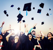 Estudantes alegres que jogam tampões da graduação no ar fotografia de stock royalty free