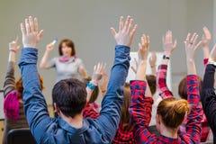 Estudantes ativos que aumentam os braços acima de pronto para responder à pergunta dos professores imagens de stock