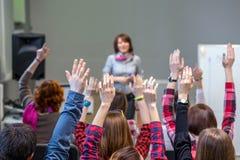 Estudantes ativos que aumentam os braços acima de pronto para responder à pergunta dos professores foto de stock