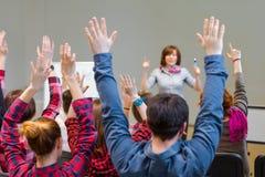 Estudantes ativos que aumentam os braços acima de pronto para responder à pergunta dos professores foto de stock royalty free