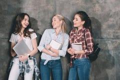 Estudantes atrativos com cadernos e portátil que está na parede Foto de Stock