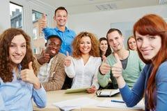 Estudantes bem sucedidos que guardaram os polegares fotografia de stock