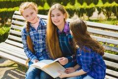 Estudantes bonitas pequenas que leem um livro e que sentam-se no banco exterior Fotografia de Stock