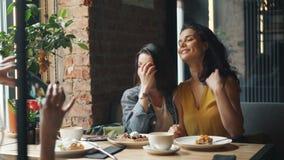 Estudantes bonitos que têm o divertimento no café que toma fotos com riso do smartphone video estoque