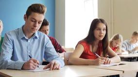 Estudantes com cadernos que escrevem o teste na escola video estoque