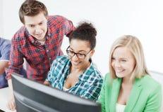 Estudantes com computador que estudam na escola Foto de Stock