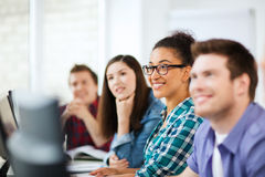 Estudantes com computadores que estudam na escola Fotos de Stock Royalty Free