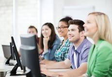 Estudantes com computadores que estudam na escola Fotografia de Stock Royalty Free