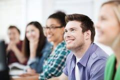 Estudantes com computadores que estudam na escola Imagens de Stock Royalty Free