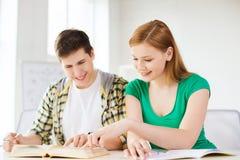Estudantes com livros de texto e livros na escola Foto de Stock Royalty Free