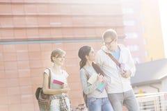 Estudantes com livros que falam ao andar contra a construção no campus universitário foto de stock royalty free