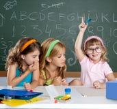Estudantes com a menina inteligente das crianças que levanta a mão foto de stock