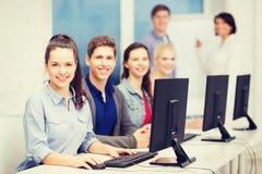 Estudantes com o monitor do computador na escola foto de stock royalty free