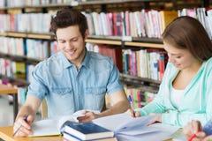 Estudantes com os livros que preparam-se ao exame na biblioteca Imagem de Stock