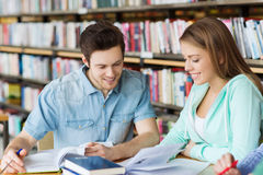 Estudantes com os livros que preparam-se ao exame na biblioteca Foto de Stock