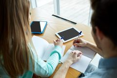Estudantes com PC da tabuleta que escrevem aos cadernos Foto de Stock