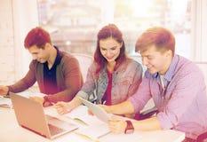 Estudantes com portátil, cadernos e PC da tabuleta Foto de Stock
