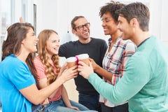 Estudantes como o café da bebida dos colegas junto imagens de stock