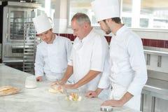 Estudantes culinários que aprendem como misturar a massa na cozinha imagens de stock royalty free