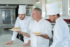 Estudantes culinários que aprendem como preparar pastelarias suculentos imagens de stock royalty free