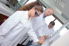 Estudantes da ciência que trabalham com produtos químicos no laboratório na universidade imagem de stock