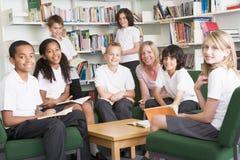 Estudantes da escola júnior que trabalham em uma biblioteca Fotos de Stock Royalty Free