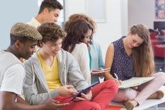 Estudantes da forma que leem suas notas Foto de Stock