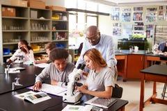 Estudantes da High School com turma de Biologia de Using Microscope In do tutor fotos de stock royalty free