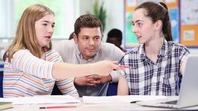 Estudantes da High School de With Two Female do professor que trabalham no portátil na sala de aula vídeos de arquivo