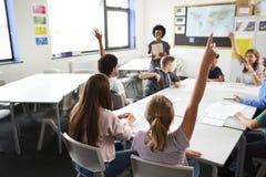 Estudantes da High School que levantam as mãos para responder à pergunta ajustada pelo professor In Classroom foto de stock