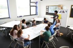 Estudantes da High School que levantam as mãos para responder à pergunta ajustada pelo professor In Classroom imagem de stock