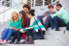 Estudantes da High School que sentam-se fora da construção com telefones Fotografia de Stock