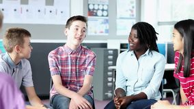 Estudantes da High School que têm a discussão informal com o professor fêmea na sala de aula