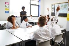 Estudantes da High School que vestem as mãos de levantamento uniformes para responder à pergunta ajustada pelo professor In Class fotografia de stock