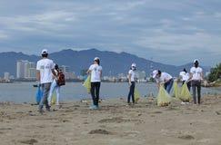 Estudantes da universidade de Nha Trang que limpa a praia foto de stock