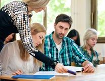 Estudantes de ajuda do professor imagens de stock