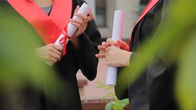 Estudantes de graduação fêmeas que mantêm diplomas amarrados com fitas vermelhas e conversa filme