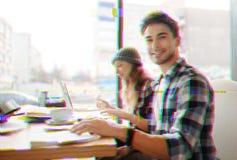 Estudantes de sorriso alegres que sentam-se em um café e que trabalham em seu projeto imagem de stock royalty free