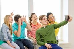 Estudantes de sorriso que fazem a imagem com PC da tabuleta fotografia de stock