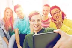 Estudantes de sorriso que fazem a imagem com PC da tabuleta imagens de stock royalty free