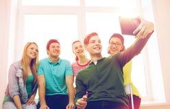 Estudantes de sorriso que fazem a imagem com PC da tabuleta imagem de stock royalty free