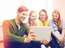 Estudantes de sorriso que fazem a imagem com PC da tabuleta imagem de stock